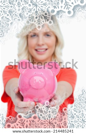 Pink piggy bank held by a smiling attractive woman against snowflakes on silver - stock photo