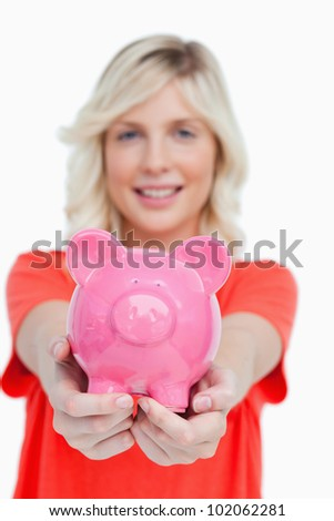 Pink piggy bank held by a smiling beautiful woman against a white background - stock photo