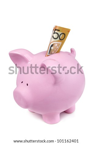 Pink piggy bank isolated on white, with Australian fifty dollar note in the slot.