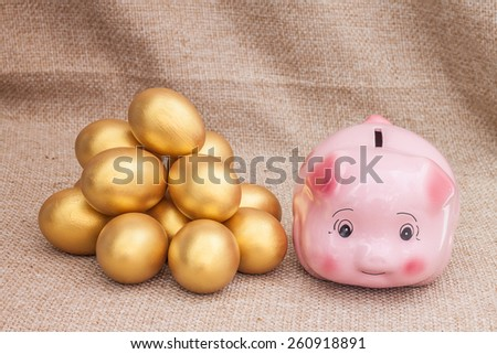 Pink piggy bank near heap of golden easter egg on brown sack - stock photo