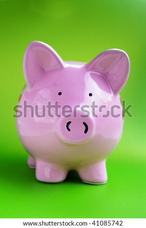 pink piggy bank on a green background - stock photo