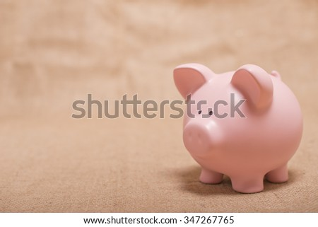 Pink Piggy Bank On Hessian Background - stock photo