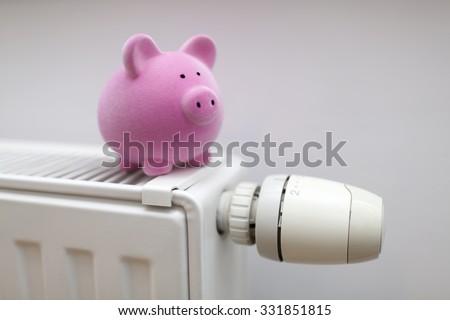 Pink piggy bank on radiator. Energy saving concept.  - stock photo