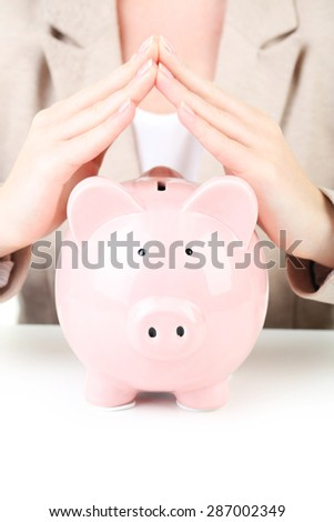 Pink piggy bank protected by hands, making roof - stock photo
