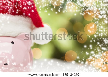 Pink Piggy Bank Wearing Red and White Santa Hat on Snowflakes with Abstract Green and Golden Snow and Light Background - Room for Your Own Text. - stock photo