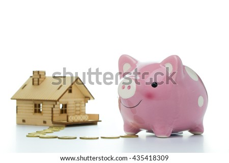Pink piggy bank with a house for home finance concept