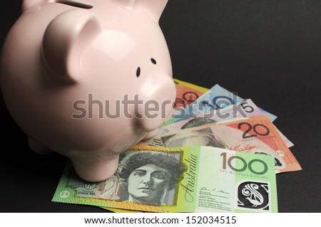 Pink Piggy Bank with Australian money against a black background, for savings concept. - stock photo
