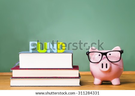 Pink Piggy bank with chalkboard in the background as concept of funding education - stock photo