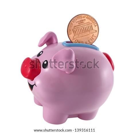 Pink piggy bank with coins falling into slot  - stock photo