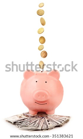 Pink piggy bank with coins falling into slot isolated on white. - stock photo