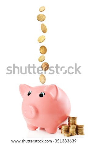 Pink piggy bank with coins falling into slot isolated on white.