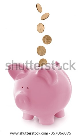 Pink piggy bank, with falling gold coins.  Isolated on white.