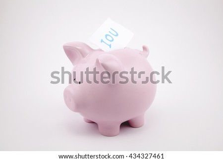 Pink piggy bank with IOU sticking out of its coin slot.  - stock photo