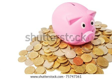 Pink piggy bank with pile coins
