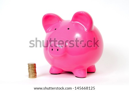 Pink Piggy bank with pound icons and GBP notes next to it - stock photo