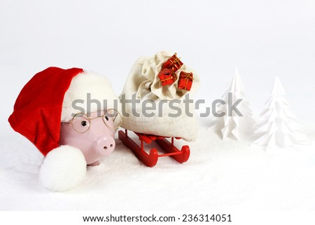 Pink piggy bank with Santa hat with pompom and glasses standing next to red sled with Santa bag with three gifts with gold bow and next to snowbound tree on snow - stock photo