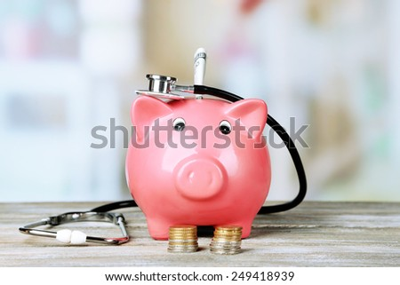 Pink piggy bank with stethoscope on light background - stock photo