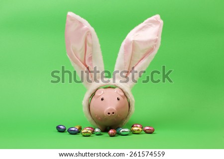 Pink piggy bank with white rabbits ears and chocolate easter eggs on green  background - stock photo