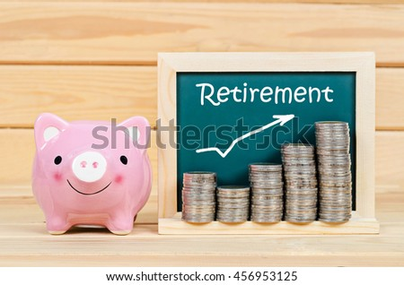 Pink piggy save money and retirement text with coin in chalkboard on wooden room.