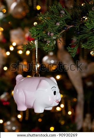 Pink piggybank hanging from branch of christmas tree - stock photo