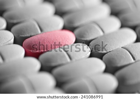 Pink pill in row of monochrome pills. Macro image. - stock photo