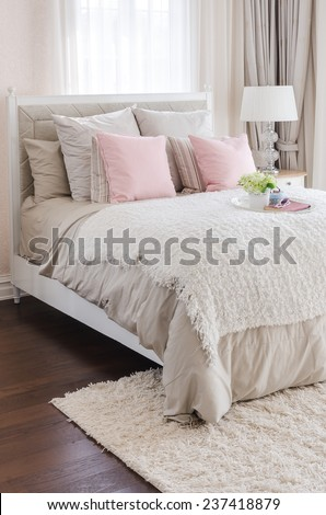 pink pillows on bed with white tray of flower - stock photo