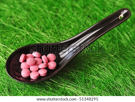 Pink pills in a black japanese spoon