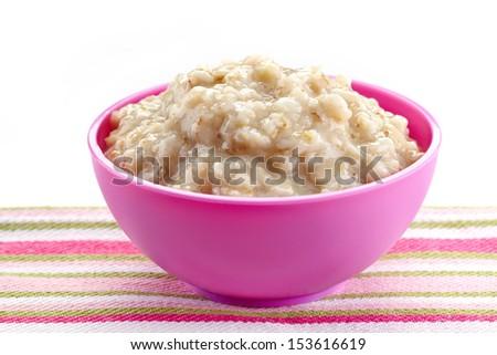 Pink plastic bowl of oats porridge. Healthy breakfast - stock photo