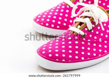 Pink polka dot canvas shoe on white background.  - stock photo