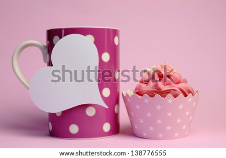 Pink polka dot coffee mug with pink cupcake and blank white heart shape gift tag for your text here, for female birthday, mothers day, or special occasion event. - stock photo