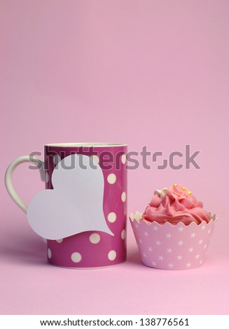 Pink polka dot coffee mug with pink cupcake and blank white heart shape gift tag for your text here, for female birthday, mothers day, or special occasion event. Vertical with copy space. - stock photo