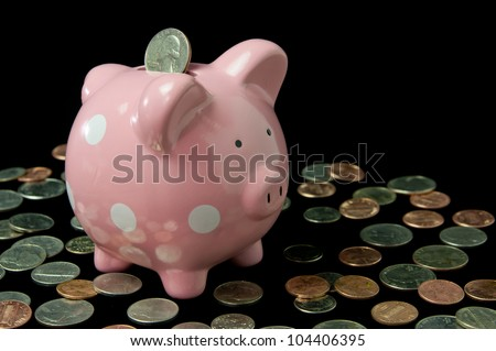Pink polka dot piggy bank surrounded by cash and coins - stock photo