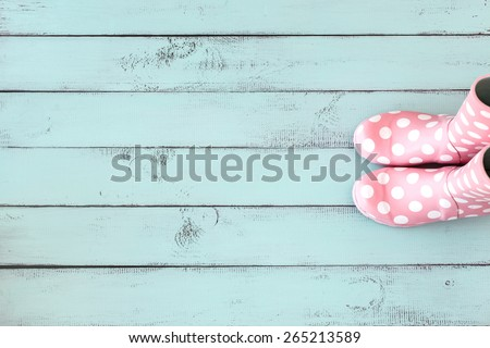 Pink polka dot rain boots on mint blue shabby chic wooden background, top view point - stock photo