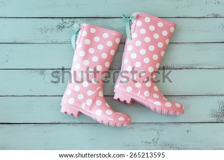 Pink polka dot shoes on mint shabby chic wooden background, top view point - stock photo