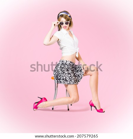 Pink pop art photo of a beautiful pinup girl strutting a beauty pose wearing 1950 style mini skirt and tied shirt with pink high heel shoes and girly accessories. Makeup and hairstyle concept - stock photo