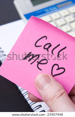 Pink post it note left with calculator and spiral notebook on office desk. Concept for office romance and St Valentine's Day.