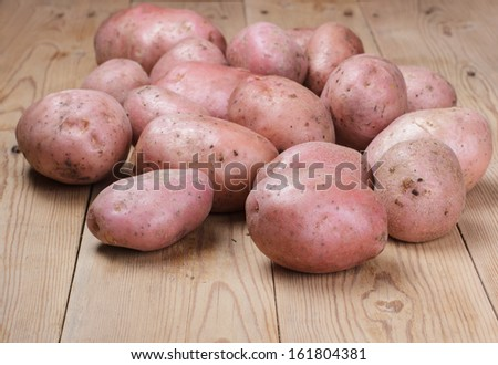 Pink potatoes on a wooden table. - stock photo