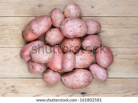 Pink potatoes on a wooden table top. - stock photo