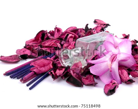 Pink potpourri with empty perfume bottle on white background - stock photo