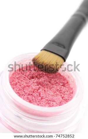 Pink powder eye shadow in jar with brush close-up on white background.