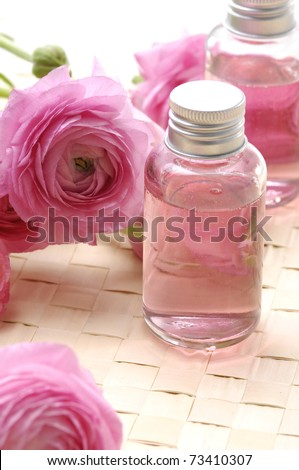 Pink ranunculus flowers and massage lotion, on woven mat - stock photo