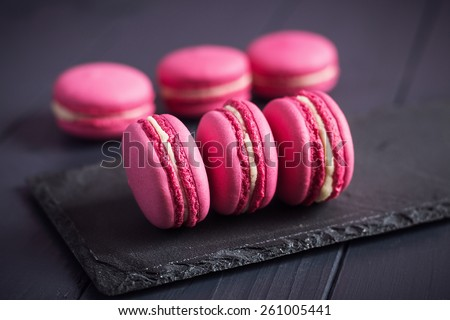 Pink raspberry macaroons on black wooden background - stock photo