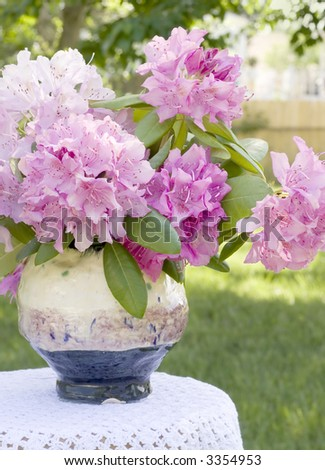Pink Rhododendrons in a handcrafted vase on a small table covered with a crocheted tablecloth. - stock photo