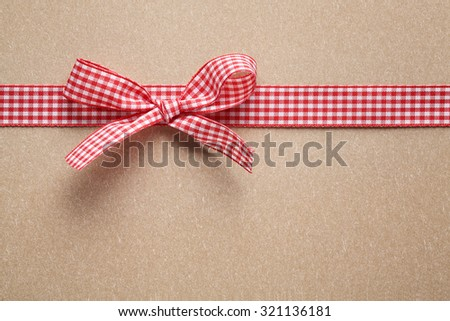 Pink ribbon bow on paper textured  background - stock photo