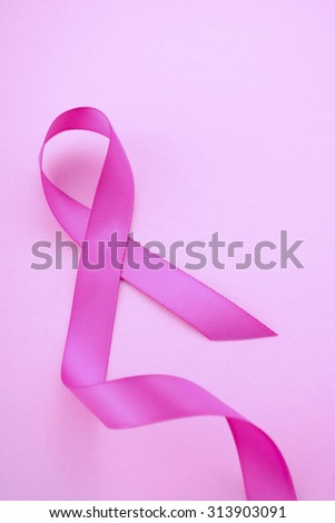 Pink Ribbon Charity for Womens Health Awareness with pink ribbon on a pink background with copy space for your text here.