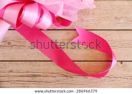 Pink ribbon on wooden background