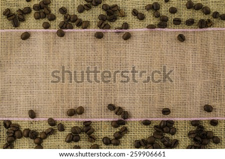 Pink ribbon with coffee beans on linen background - stock photo