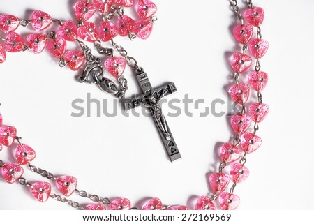 Pink rosary cross medal on the white background - stock photo