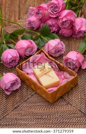 pink rose and petals with soap in basket on mat