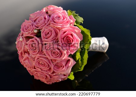 Pink rose bridal bouquet on a black background - stock photo